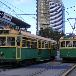 Two cream and green W class trams at Docklands next to Etiha'd Stadium.
