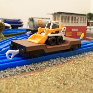 Re-painted Plarail Lowmac wagon, with a Matchbox, skid steer shovel load. 
